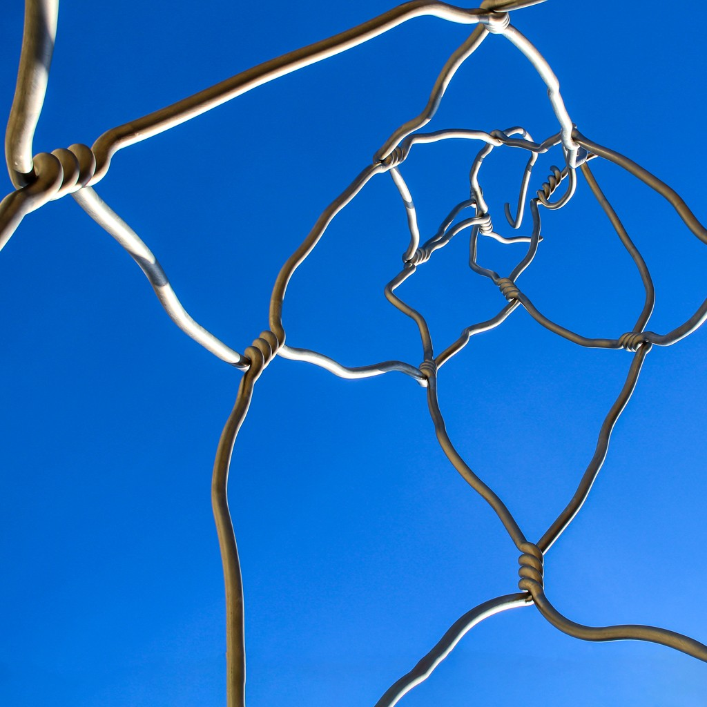 A chain-link fence sculpture in Barcelona, Spain, viewed from below.